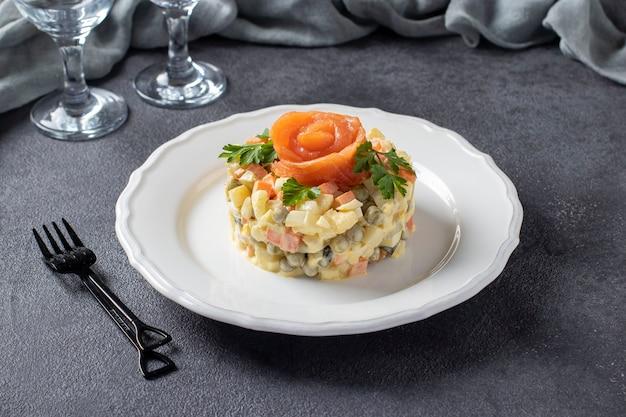 Insalata russa tradizionale olivier con salmone salato su fondo grigio scuro.