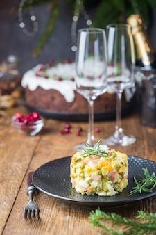 Insalata russa tradizionale con verdure cotte con maionese in un piatto di legno