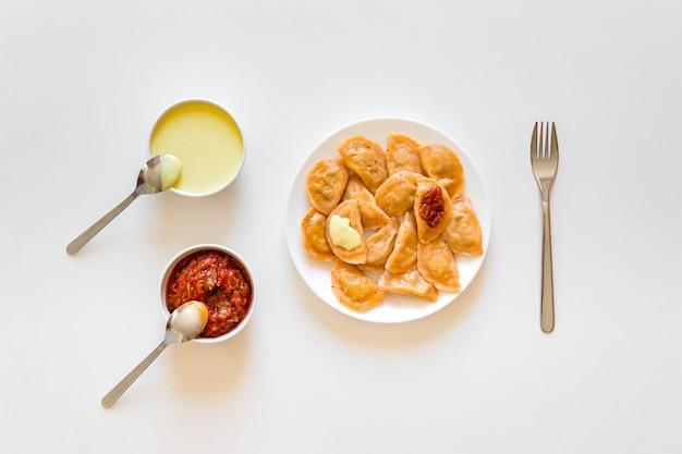 Gnocchi tradizionali di vareniki dell'alimento russo ed ucraino con senape e salsa al pomodoro su un piatto bianco.