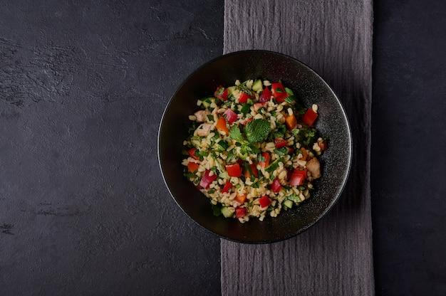 Tabbouleh di insalata tradizionale fatto di bulgur o couscous di carne di pollame prezzemolo e menta in una ciotola scura con