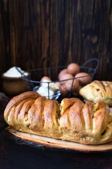 Una torta salata tradizionale della cucina russa chiamata kulebyaka. ingredienti per la pasta burro, farina, uova. torta con carne e cavolo. fondo rustico scuro. avvicinamento