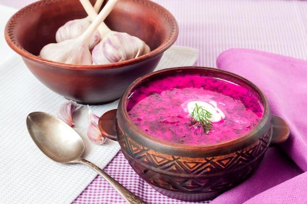 Zuppa di barbabietola fredda tradizionale slava con uova sode di cetriolo e verdure in una ciotola rustica