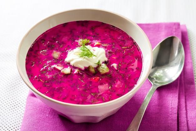 Zuppa di barbabietola fredda tradizionale slava con uova sode di cetriolo e verdure in una ciotola bianca sul panno viola