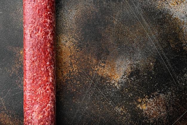Insieme tradizionale della salsiccia affumicata del salame, sulla vecchia tavola rustica scura, disposizione piana di vista superiore