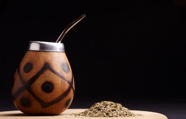 Tè yerba mate tradizionale sudamericano nel cerchio di zucca e bombilla. sfondo nero