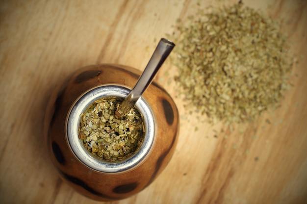 Tè yerba mate tradizionale sudamericano nel cerchio di zucca e bombilla. fondo in legno