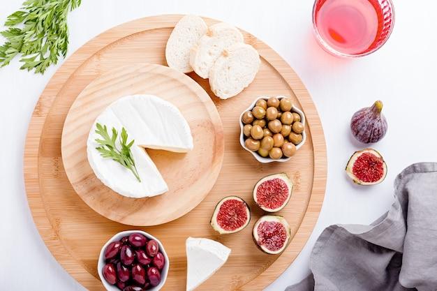 Antipasti di cucina tradizionale spagnola con formaggio brie bianco, fichi, olive e vino rosato su tavolo bianco