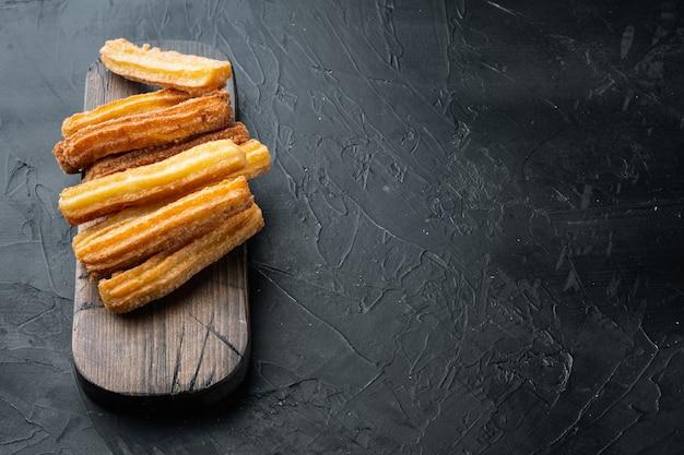 Churros di dessert tradizionali spagnoli con zucchero e cioccolato, sulla tavola nera, copyspace