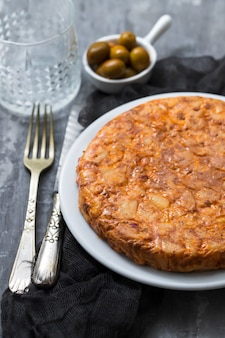 Cibo tradizionale spagnolo tortilla con patate sul piatto bianco e olive in una piccola ciotola su fondo in ceramica.