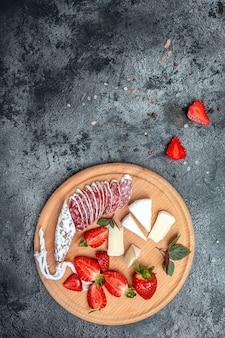 Tradizionale spagnolo fuet sottile salsiccia secca con formaggio camembert, fragole e bicchiere di vino rosato su sfondo scuro. immagine verticale. vista dall'alto.