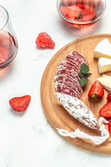 Tradizionale spagnolo fuet sottile salsiccia secca con formaggio camembert, fragole e bicchiere di vino rosato su sfondo bianco. immagine verticale. vista dall'alto.