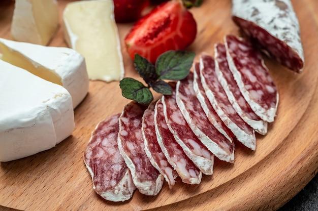 Salsiccia secca sottile tradizionale del fuet spagnolo con muffa nobile, formaggio camembert, fragole. sfondo di ricetta alimentare. avvicinamento.