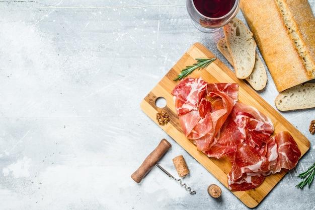 Prosciutto spagnolo tradizionale con ciabatta e vino rosso. su un rustico.