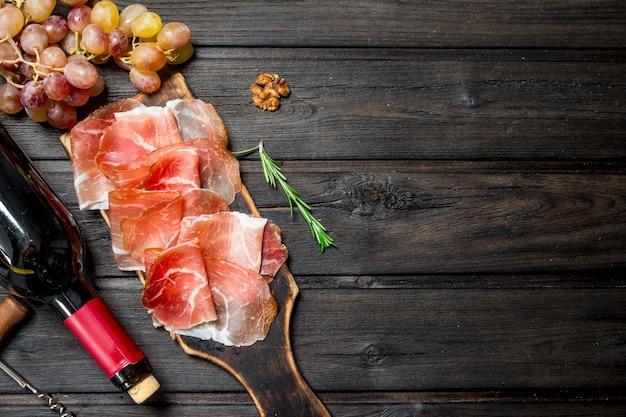 Prosciutto spagnolo tradizionale con uva e vino rosso. su uno sfondo di legno.