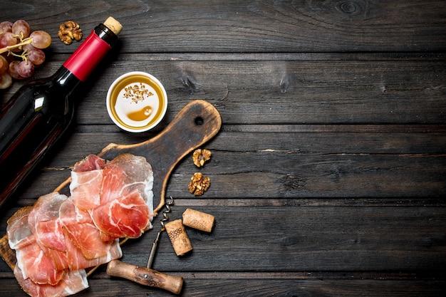 Prosciutto spagnolo tradizionale con vino rosso. su uno sfondo di legno.