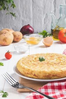 Frittata spagnola tradizionale con patate e cipolla con ingredienti su fondo rustico chiaro, formato verticale. tapas spagnole.