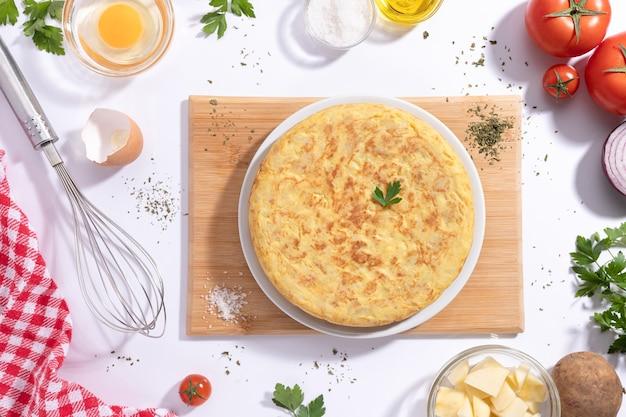 Frittata spagnola tradizionale con patate e cipolla con ingredienti su sfondo bianco, piatto. tapas spagnole.