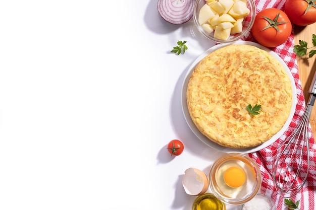 Frittata spagnola tradizionale con patate e cipolla con ingredienti su sfondo bianco con spazio di copia, piatto. tapas spagnole.