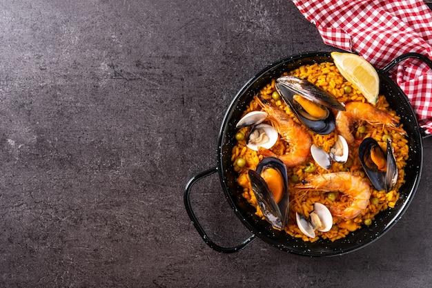 Paella spagnola tradizionale dei frutti di mare su fondo nero