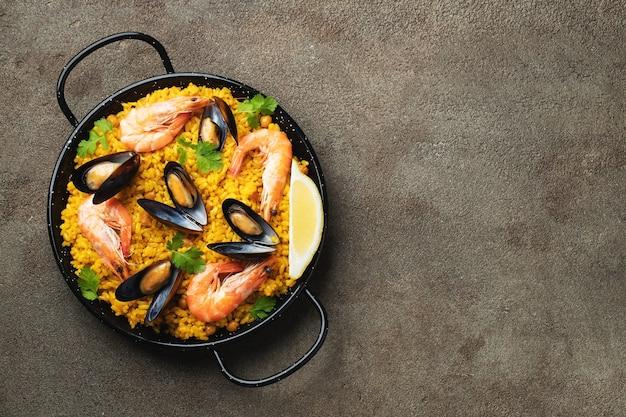 Tradizionale paella spagnola di frutti di mare in padella su elegante sfondo marrone, vista dall'alto