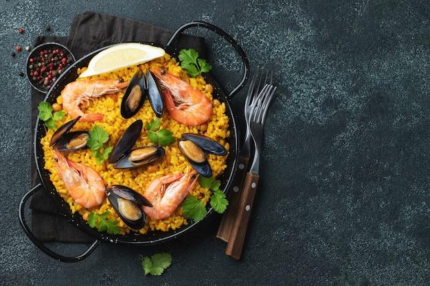 Tradizionale paella spagnola di pesce in padella su elegante sfondo scuro, vista dall'alto