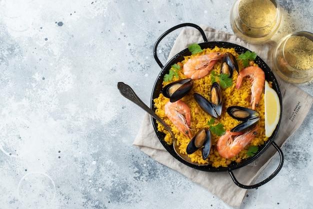 Tradizionale paella spagnola di pesce in padella su elegante sfondo di marmo chiaro, vista dall'alto