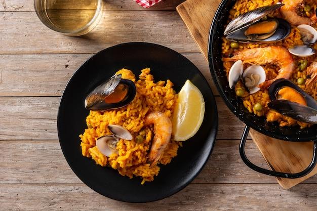 Paella spagnola tradizionale dei frutti di mare sulla tavola di legno