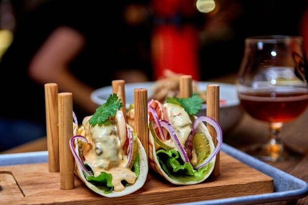Tacos di maiale messicano di strada tradizionale con carne di manzo, pomodori, avocado, peperoncino e cipolle in tortilla di mais giallo chiamato al pastor