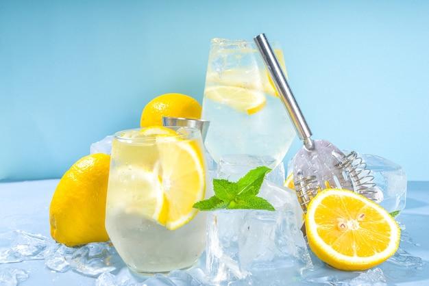 Limonata cocktail rinfrescante estiva tradizionale fredda, con fette di limone e un sacco di ghiaccio tritato e piedistalli ghiacciati su sfondo blu