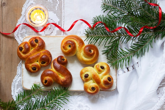 Panini tradizionali svedesi allo zafferano di varie forme su uno sfondo chiaro. messa a fuoco selettiva.