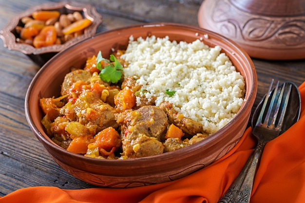 Piatti tradizionali tajine, couscous e insalata fresca sul tavolo di legno rustico. tagine carne di agnello e zucca.