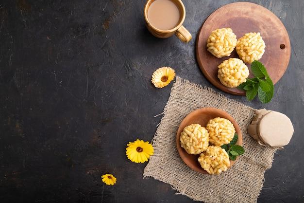 Chak-chak tradizionale della caramella tartara fatta di pasta e miele con una tazza di caffè su cemento nero e tessuto di lino. vista dall'alto.