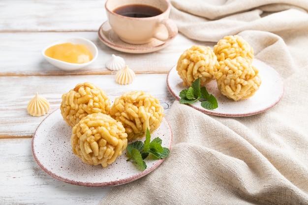 Chak-chak tradizionale della caramella tartara fatta di pasta e miele con una tazza di caffè su un fondo di legno bianco e tessuto di lino. vista laterale, da vicino.