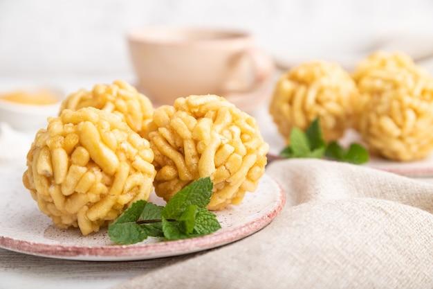 Chak-chak della caramella tartara tradizionale fatto di pasta e miele con la tazza di caffè sulla tavola di legno bianca e sul tessuto di tela.