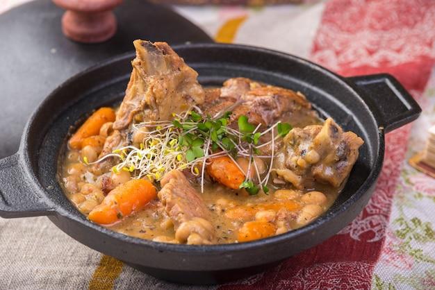 Zuppa densa tradizionale a base di crauti con maiale, costine di maiale affumicate, salsicce, capperi e limone.