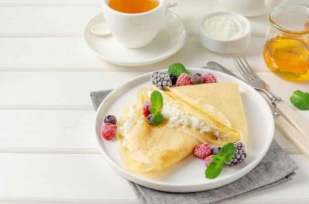 Frittelle sottili tradizionali o crepes con ricotta e uvetta con frutti di bosco, miele e panna acida su un fondo di legno bianco. cibo per maslenitsa. copia spazio.