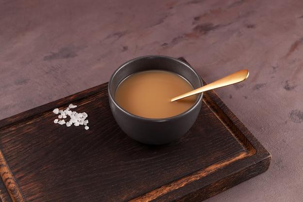 Tè al burro tibetano tradizionale o tè zangolato nella ciotola scura sul tagliere
