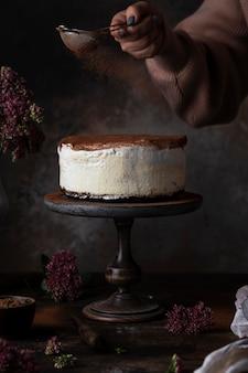 Torta tiramisù tradizionale con caffè e cioccolato su fondo scuro