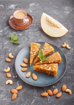 Tradizionale cezerye di caramelle turche a base di melone caramellato, noci, nocciole, anacardi, in un piatto di ceramica blu e una tazza di caffè su uno sfondo di cemento nero. vista laterale, da vicino.