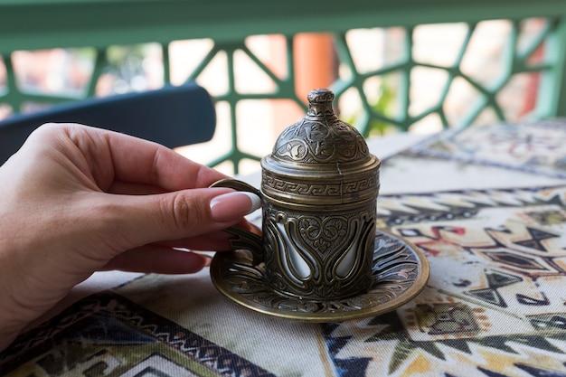 Caffè turco tradizionale. caffè orientale sul tavolo in una tazza di rame. una mano femminile tiene una tazza. tbilisi, georgia. foto di alta qualità
