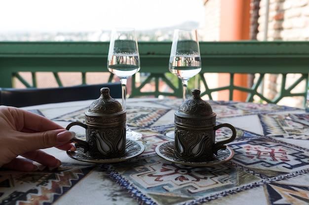 Caffè turco tradizionale. caffè orientale sul tavolo in una tazza di rame. una mano femminile tiene una tazza. due bicchieri di chacha georgiana. tbilisi, georgia. foto di alta qualità