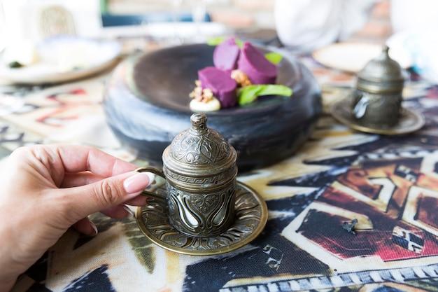 Caffè turco tradizionale. caffè orientale sul tavolo in tazze di rame. una mano femminile tiene una tazza. dolce georgiano. tbilisi, georgia. foto di alta qualità