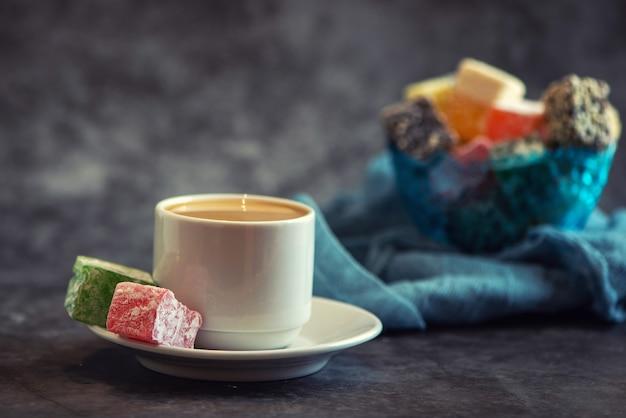 Delizia turca tradizionale e tazza di caffè su sfondo grigio
