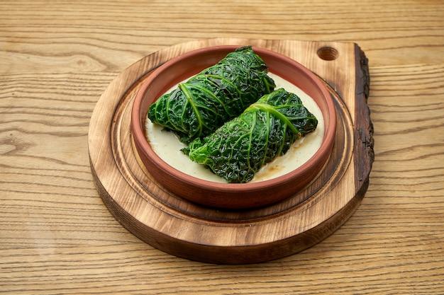 Un piatto tradizionale ucraino sono involtini di cavolo ripieni con carne macinata e riso in una ciotola con salsa rossa e panna acida