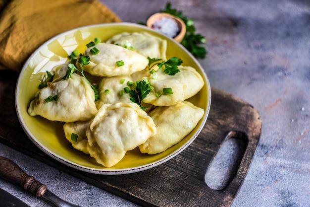Vareniki o gnocchi di patate in streaming ucraini tradizionali serviti in una ciotola e erbe verdi