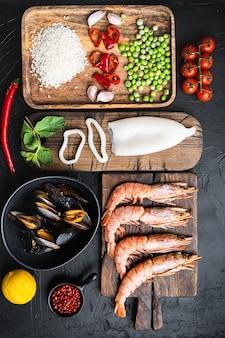 Ingredienti di mare della paella valenciana tradizionale con gamberi, cozze, riso e spezie su nero