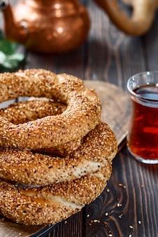 Pane bianco tradizionale con semi di sesamo per colazione, un bicchiere di armudu con tè rosso su un tavolo di legno