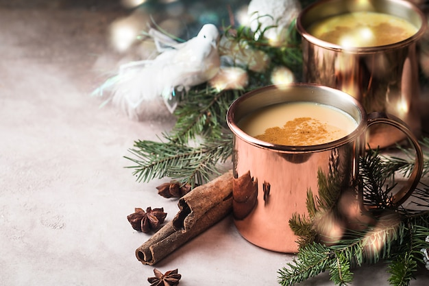 Tradizionale zabaione invernale in boccali di rame con rum di latte e cannella spolverata di noce moscata grattugiata decorazioni natalizie