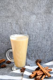 Zabaione invernale tradizionale in tazza di vetro con latte, cannella e anice stellato con panna montata. caffè