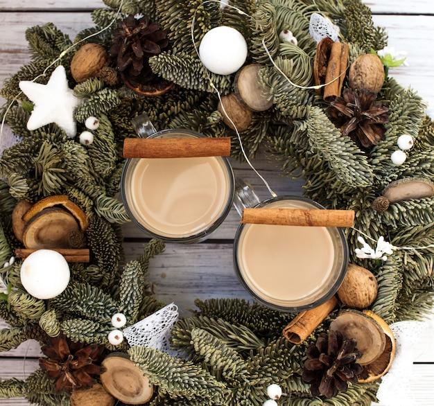 Zabaione invernale tradizionale in tazza di vetro con latte, rum e cannella, decorazioni natalizie.